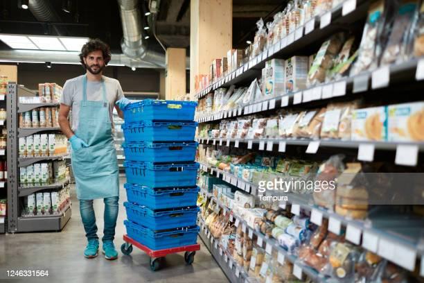 um funcionário do supermercado parado ao lado de uma pilha de caixas e olhando para a câmera. - visão geral - fotografias e filmes do acervo