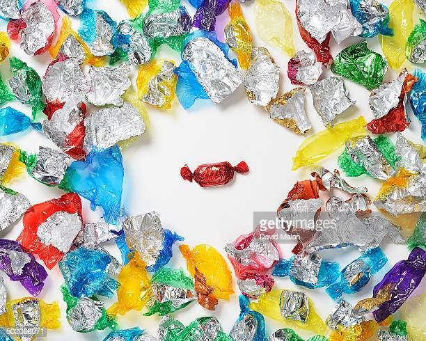 one sweet amongst empty wrappers - candy wrapper stock photos and pictures