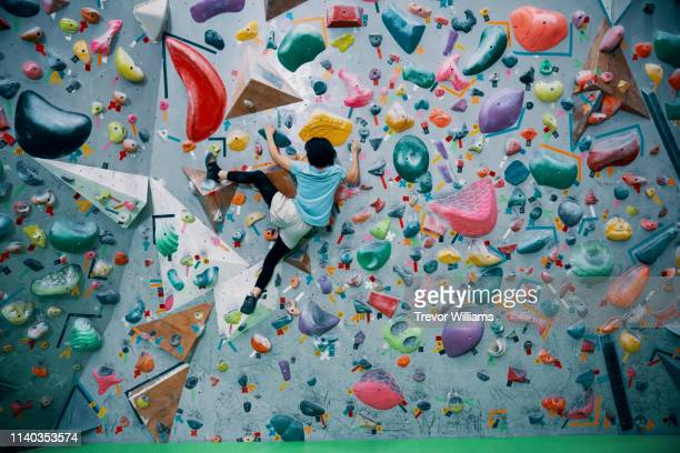 one teenage girl climbing a bouldering wall at a rock climbing gym - klettern stock-fotos und bilder