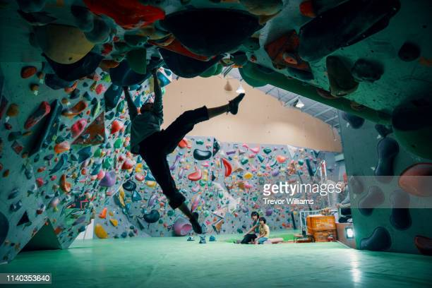 one teenage girl climbing a bouldering wall at a rock climbing gym - クライミングウォール ストックフォトと画像