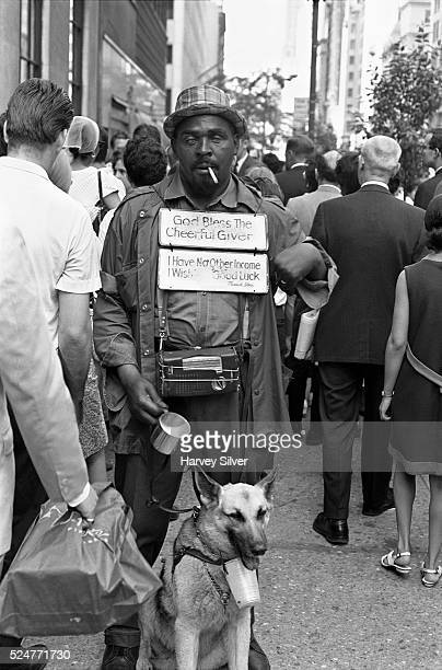 One the day of Robert Kennedy's funeral a blind man with a seeingeye dog holds his cup for passers by near the location of the funeral