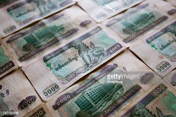 One thousandkyat bank notes are arranged for a photograph in Putao Myanmar on Saturday March 17 2012 Myanmar next week holds the most inclusive...