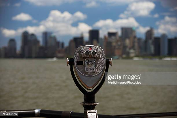 One tourist sight-seeing camera with view of Manhattan skyline from Liberty Island, NY, USA