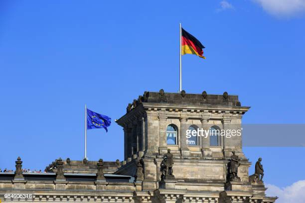 One tower of the Reichstag building with german and EU- flag (german parliament building) - Berlin, Germany