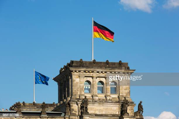 One tower of the Reichstag building with german and EU-flag (german parliament building) - Berlin, Germany