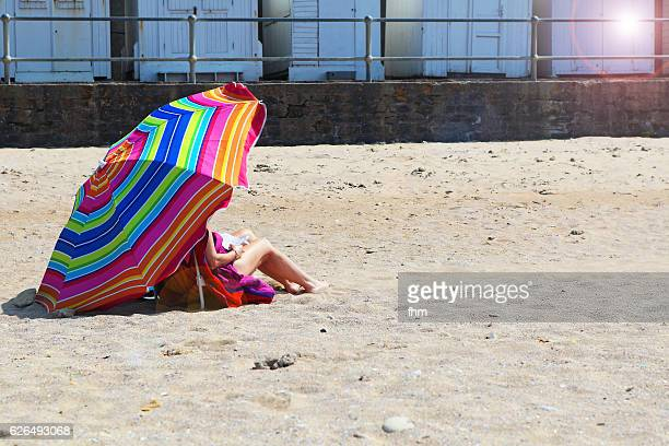 One unrecognizable woman, sitting under a sun umbrella on the beach