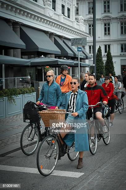 One very stylish fashion oriented girl wearing retro styled sunglasses and riding her bicycle in the streets of Copenhagen