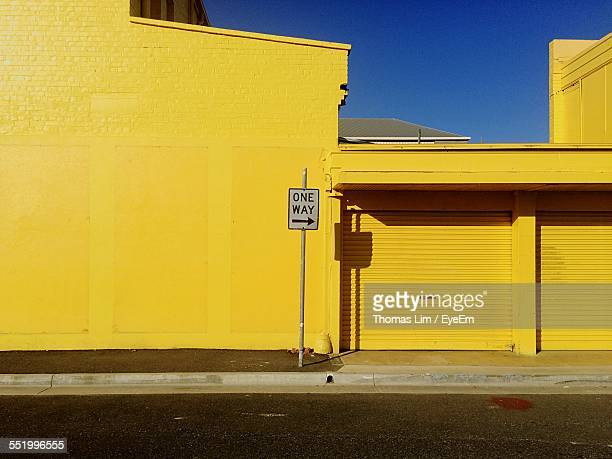 one way sign against yellow building - cartello chiuso foto e immagini stock