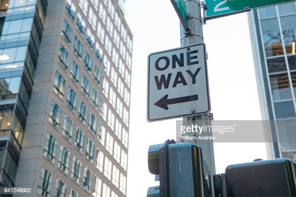 'One Way' street sign on urban street