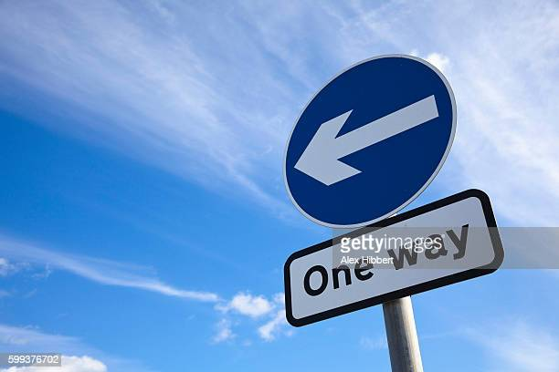 one way traffic sign against blue sky, uk - one direction stock pictures, royalty-free photos & images