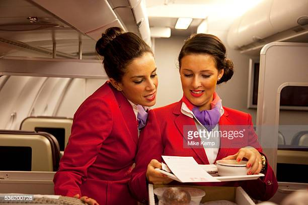 One week away from getting their 'wings' these flight attendants proudly wear their red uniforms as they undergo an in flight training session...