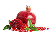 one whole and part of a pomegranate with pomegranate seeds and leaves isolated on white background