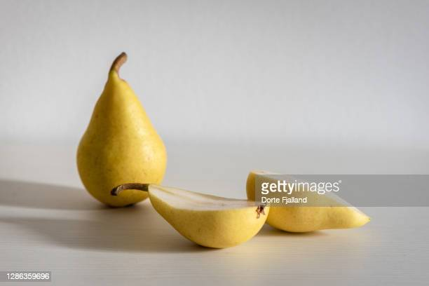 one whole pear and one half pear on a white background - dorte fjalland stock pictures, royalty-free photos & images