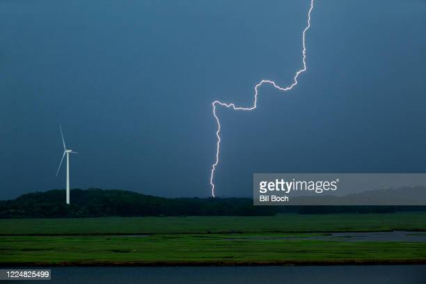 one wind turbine with a lightning flash during thunderstorm - 泥沼地 ストックフォトと画像