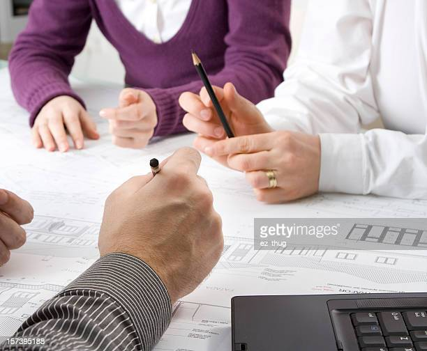 One woman and two men at a desk looking over plans