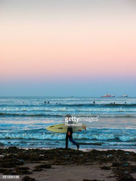 One Woman Carrying Surf Board at Shoreline Aberdeen Scotland