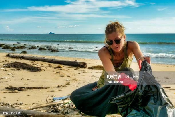 una mujer recogiendo basura andamán orilla del mar - activista fotografías e imágenes de stock