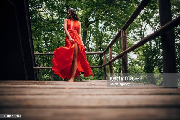 one woman in red dress dancing alone in nature - red dress stock pictures, royalty-free photos & images