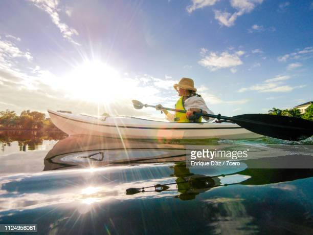 one woman kayaking on a lake, wide angle - wide angle stock pictures, royalty-free photos & images
