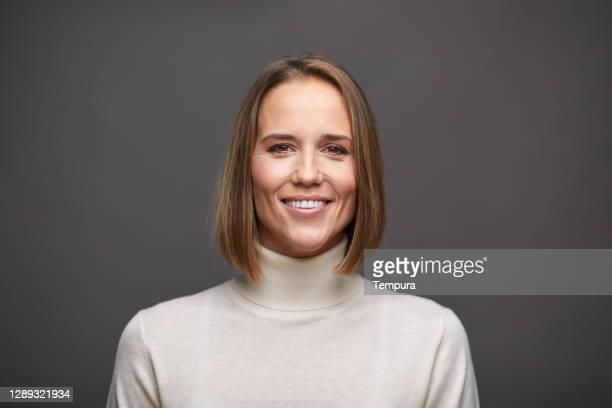 en kvinna tittar på kameran och bär en polotröja. - mellan 30 och 40 bildbanksfoton och bilder