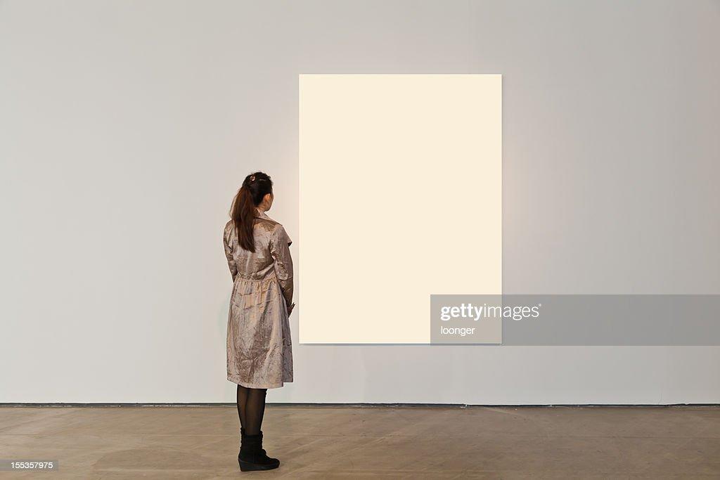 Eine Frau, die auf weißen Rahmen in Kunstgalerie : Stock-Foto
