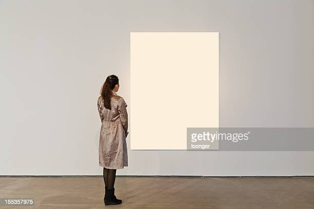 one woman looking at white frame in an art gallery - rear view photos stock photos and pictures