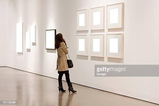 one woman looking at white frames in an art gallery - konstmuseum bildbanksfoton och bilder