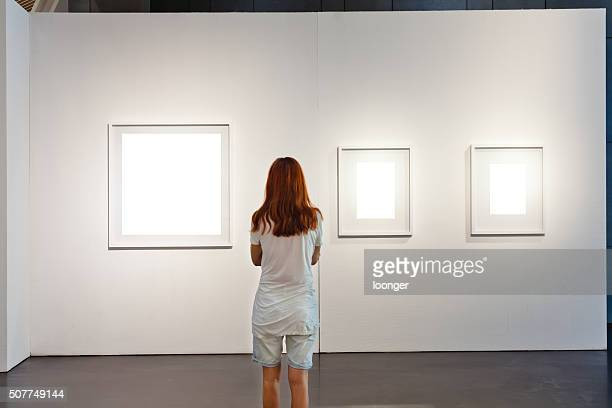 one woman looking at white frames in an art gallery - art gallery stock pictures, royalty-free photos & images