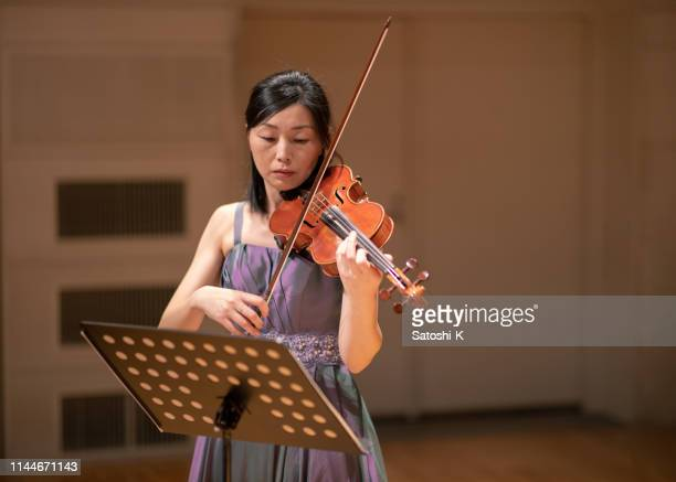 one woman playing violin at concert hall - classical musician stock pictures, royalty-free photos & images