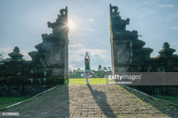 One woman practicing yoga in Bali, traditional gate, Indonesia