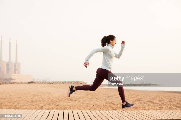 one woman running and exercising in barcelona near the beach. - sports training drill stock pictures, royalty-free photos & images