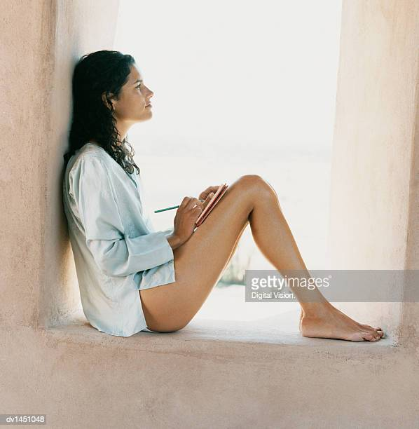 One Woman Sits Leaning on a Stone Windowsill Writing in her Diary