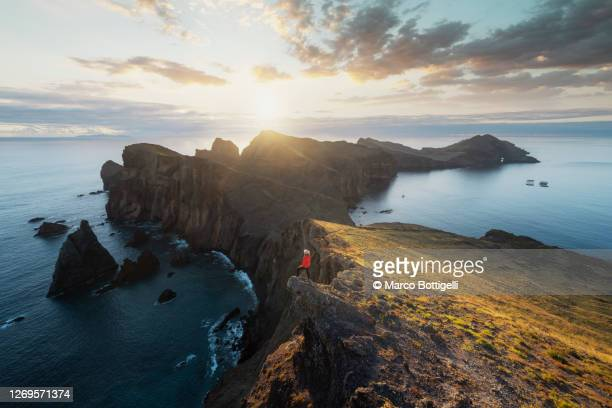 one woman standing on a cliff at sunrise in madeira - madeira fotografías e imágenes de stock