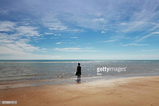 One woman standing on the beach and looking to the horizon