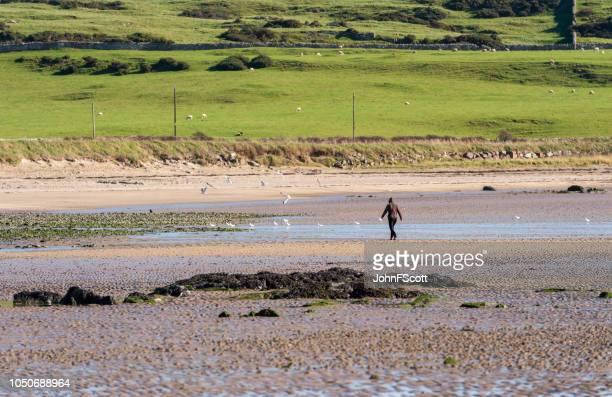 One woman walking on a quiet Scottish beach