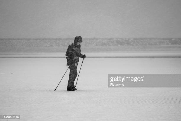 One woman walking on an empty beach during a snowstorm in midwinter