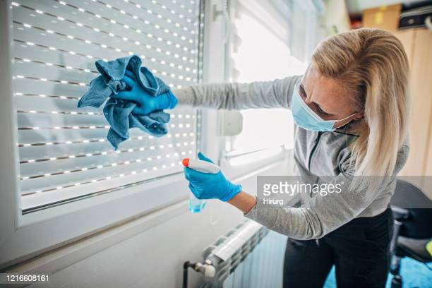 一人の女性が拭いて窓に消毒をする - 手袋 ストックフォトと画像