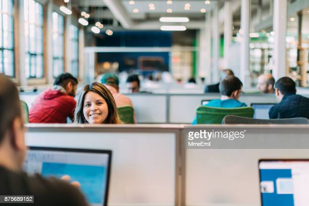 one woman with a group of men studying or working in an open plan area. startup. female rising. feamle leaders. bring your own device area. - área sem divisões imagens e fotografias de stock