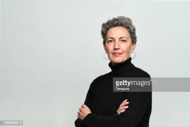 one woman with arms crossed over her chest looking at the camera. - waist up stock pictures, royalty-free photos & images