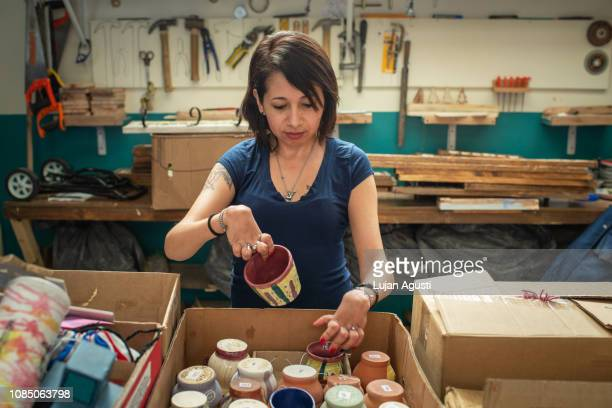 one woman with differing abilities at a ceramics studio - disabilitycollection stock-fotos und bilder