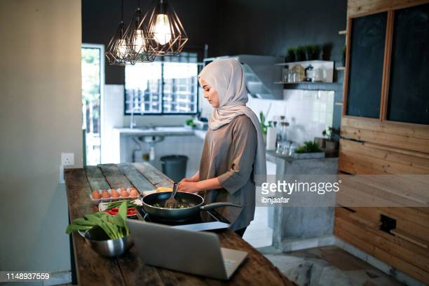 one women cooking in kitchen with laptop - eid al adha stock pictures, royalty-free photos & images