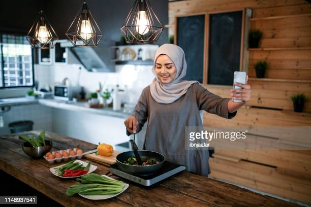 one women looking at phone while cooking - beautiful ramadan stock pictures, royalty-free photos & images