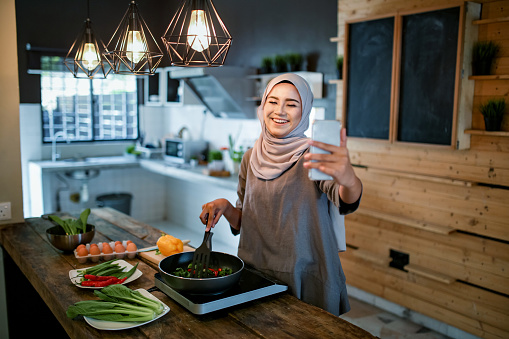 One women looking at phone while cooking 1148937545