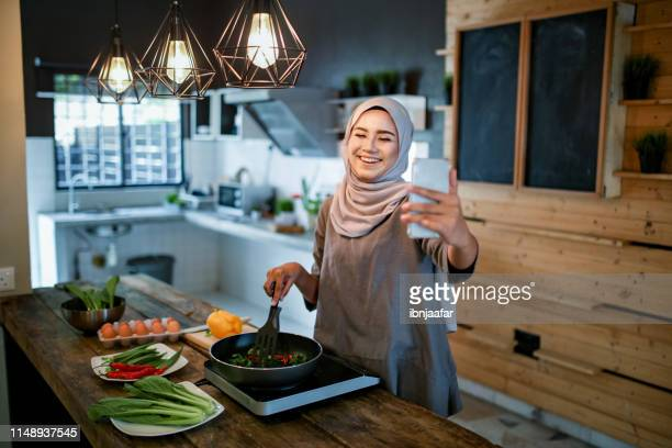 One women looking at phone while cooking