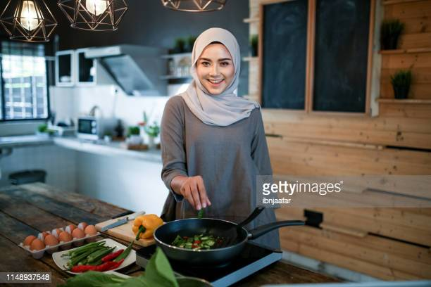 one women looking at phone while cooking - malaysia stock pictures, royalty-free photos & images