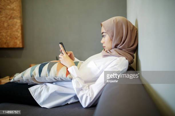 one women looking at the phone - eid ul fitr photos stock pictures, royalty-free photos & images