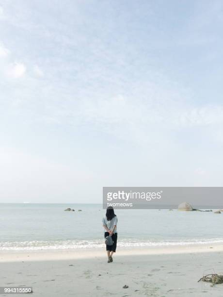 One women walking by seashore.