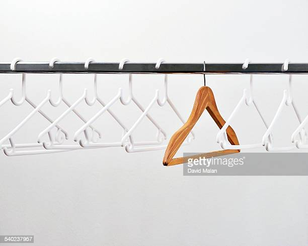 One wooden coat hanger amongst plastic hangers