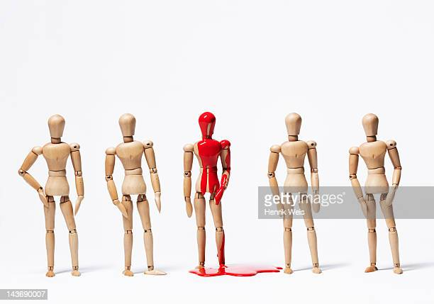 one wooden figurine in paint with others - human representation stock pictures, royalty-free photos & images