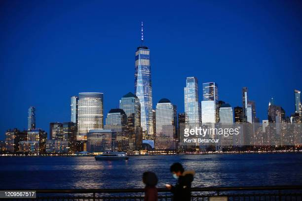 One World Trade Center is lit in blue on April 9, 2020 as seen from Jersey City, New Jersey. Landmarks and buildings across the nation are displaying...